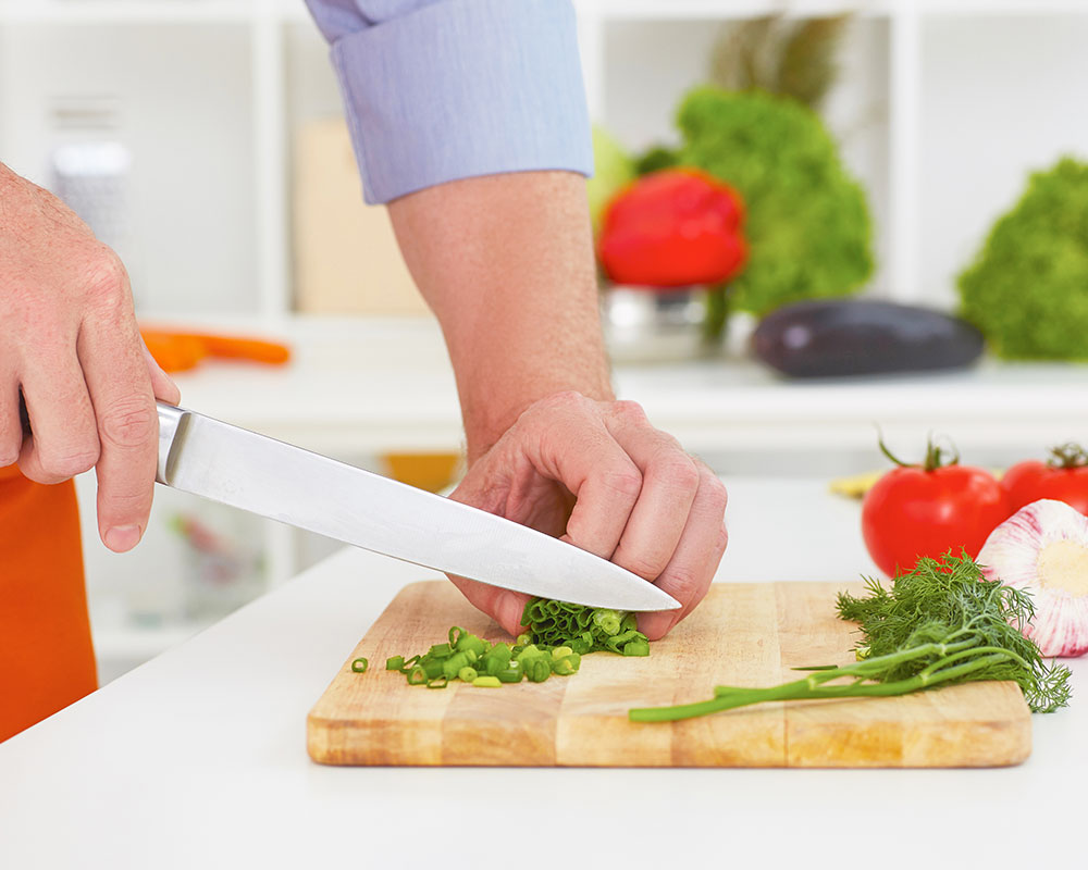 Chef chopping fresh food in an office kitchen